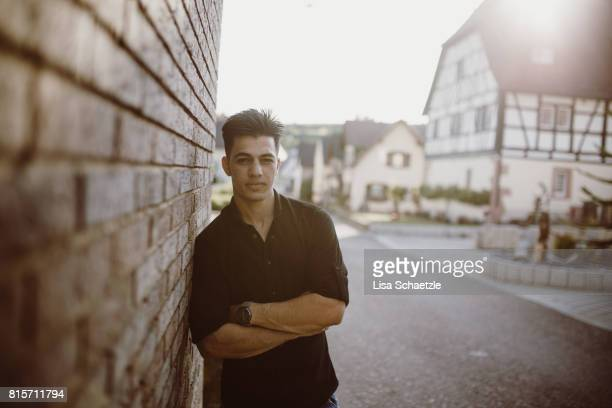 portrait of a young man leaning on a wall - emigration och immigration bildbanksfoton och bilder