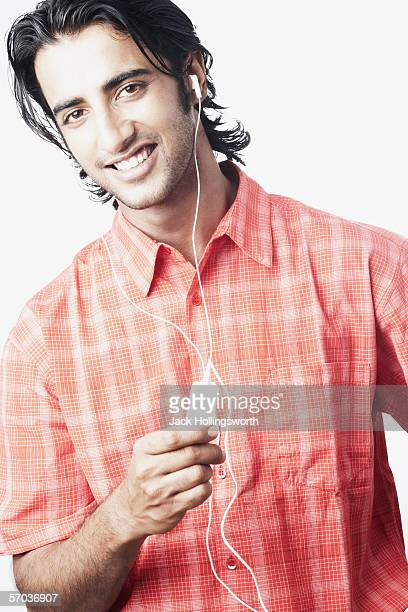 Portrait of a young man listening to an MP3 player