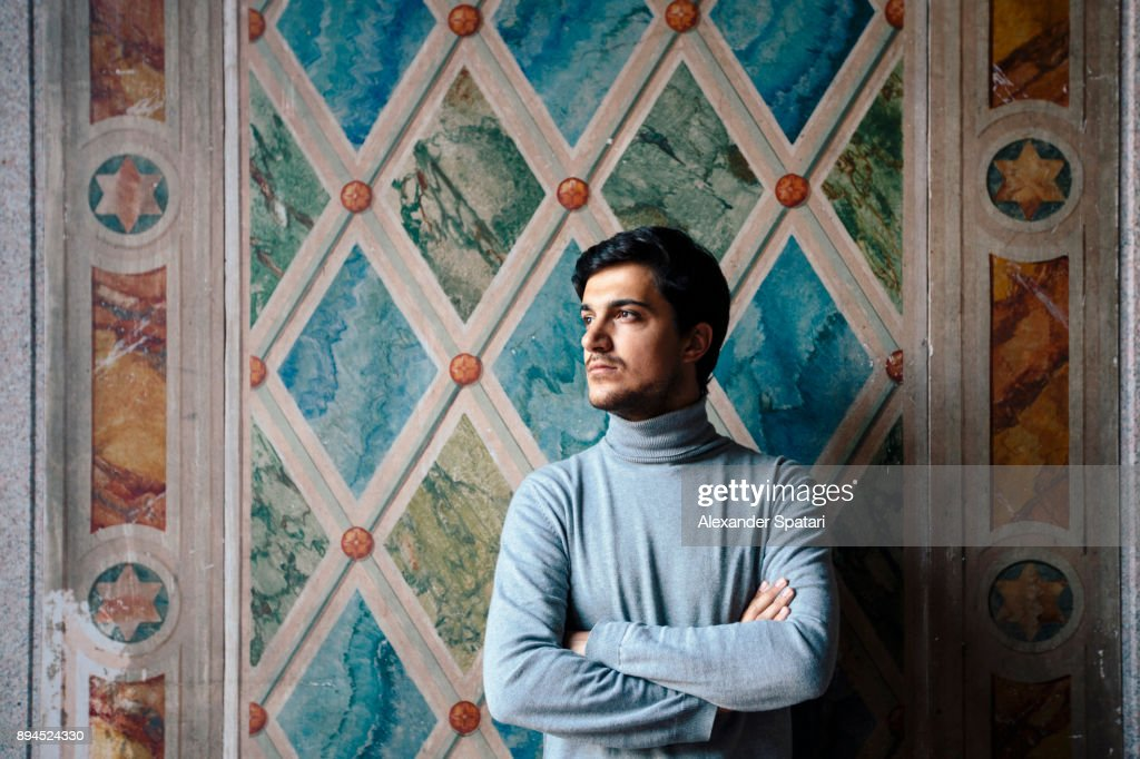 Portrait of a young man looking away arms crossed against the wall : Stock Photo