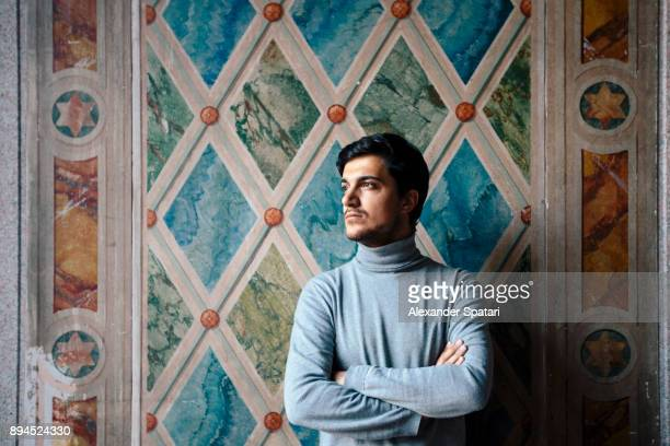 Portrait of a young man looking away arms crossed against the wall