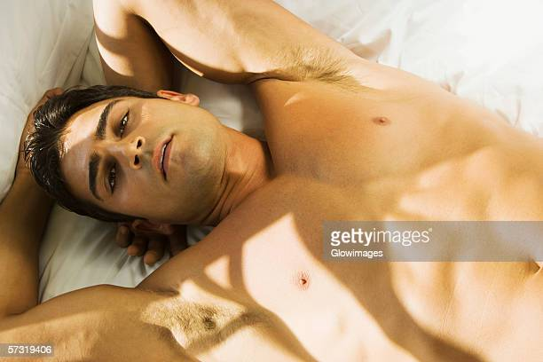 portrait of a young man lying on his back looking serious - male belly button stock photos and pictures