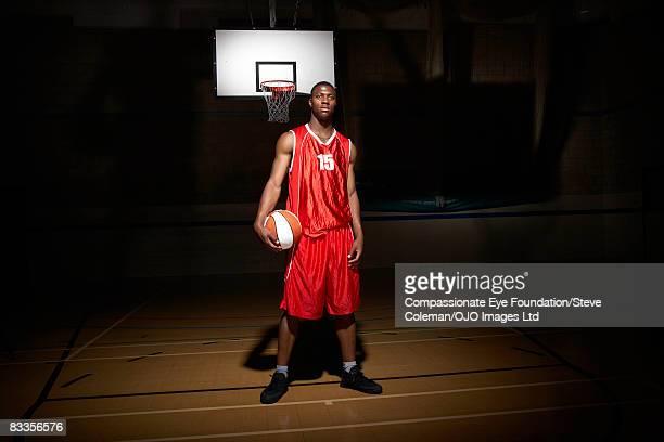 portrait of a young man on the basketball court - バスケットボールのユニフォーム ストックフォトと画像