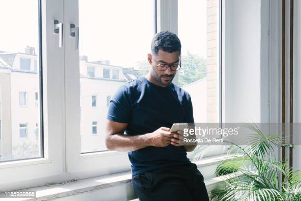 portrait of a young man on the phone indoors - one person stock pictures, royalty-free photos & images