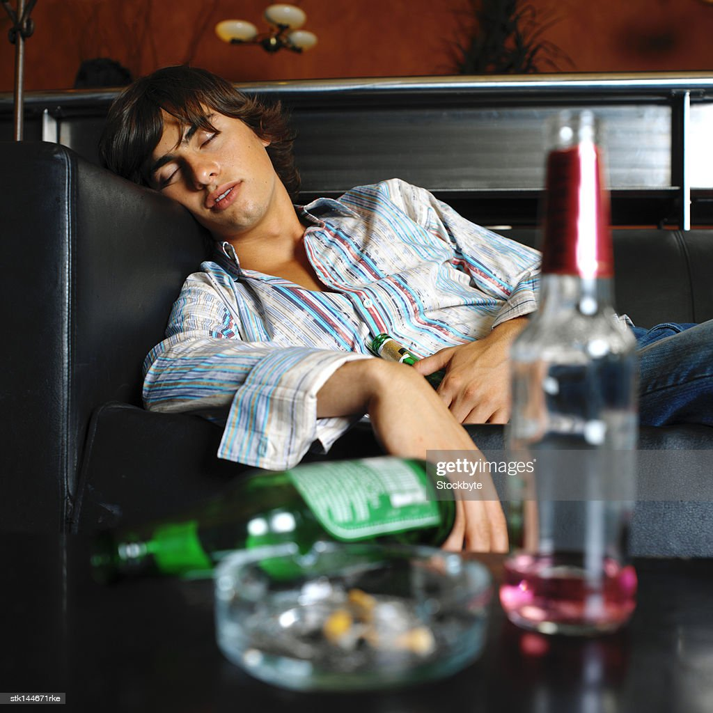 portrait of a young man passed out on the couch : Stock Photo
