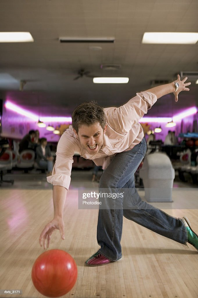 Portrait of a young man playing bowling at a bowling alley : Foto de stock