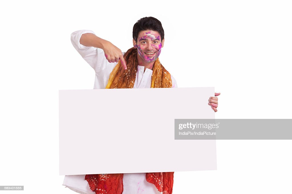 Portrait of a young man pointing to a white board : Stock Photo