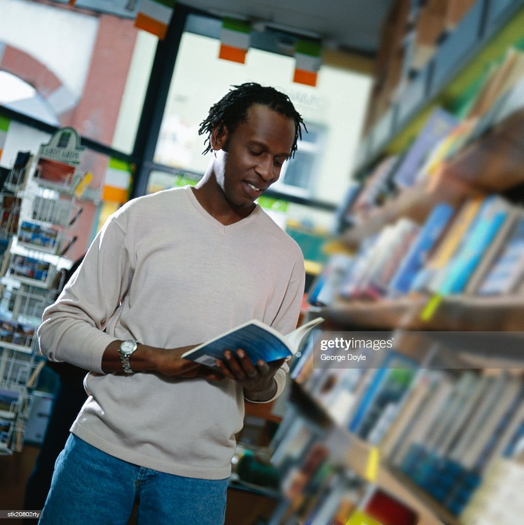 portrait of a young man reading a book in a bookstore stock photo