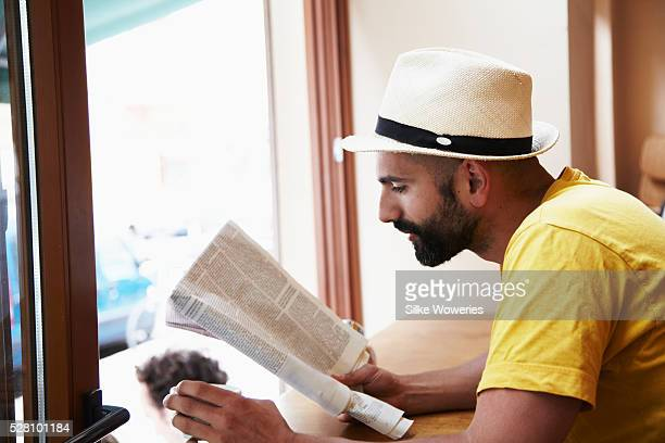 portrait of a young man reading the newspaper in a cafe