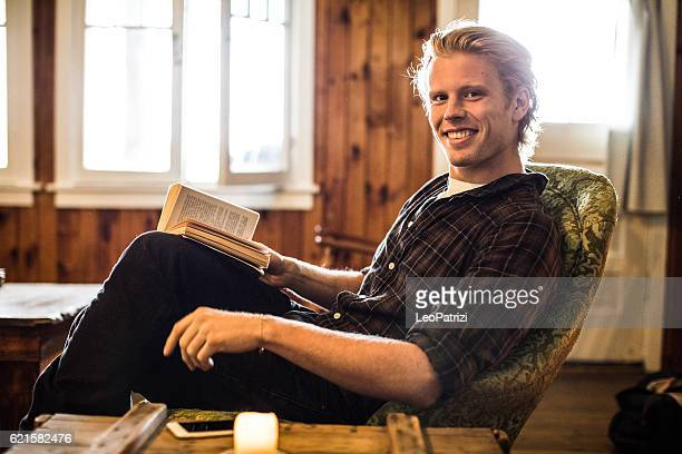 Portrait of a young man relaxing reading a book