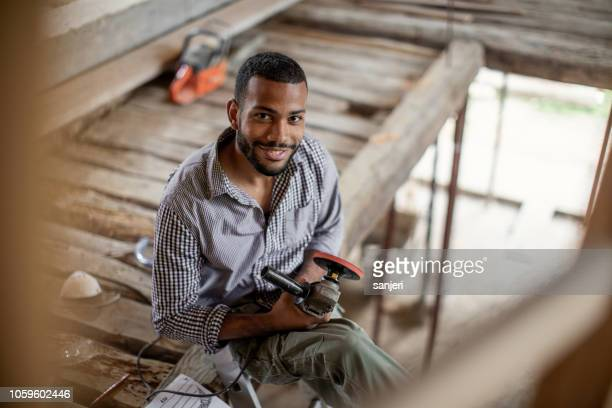 portrait of a young man renovating old floor - restoring stock pictures, royalty-free photos & images