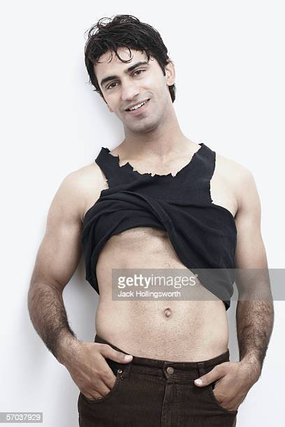portrait of a young man showing his abdomen - male belly button stock photos and pictures