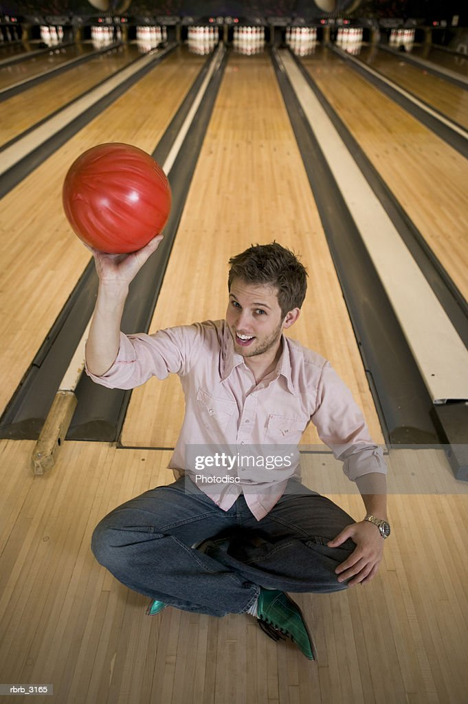 Portrait of a young man sitting at a bowling alley holding a bowling ball : Foto de stock