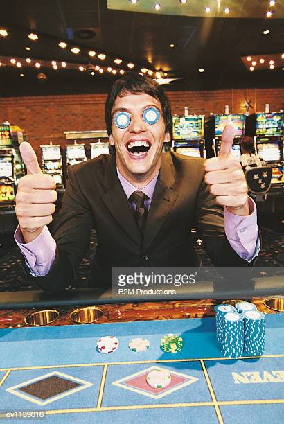 portrait of a young man sitting at a casino table with his thumbs up and gambling chips covering his eyes - gambling table stock pictures, royalty-free photos & images