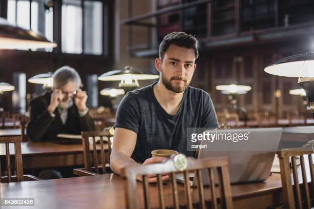 Portrait of a young man sitting in the library, studying