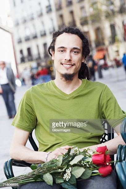 portrait of a young man sitting on a chair with a bunch of roses on his lap - vネック ストックフォトと画像