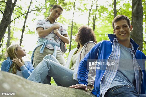 portrait of a young man sitting on a rock and smiling with his friends in the background - freundschaft stock pictures, royalty-free photos & images