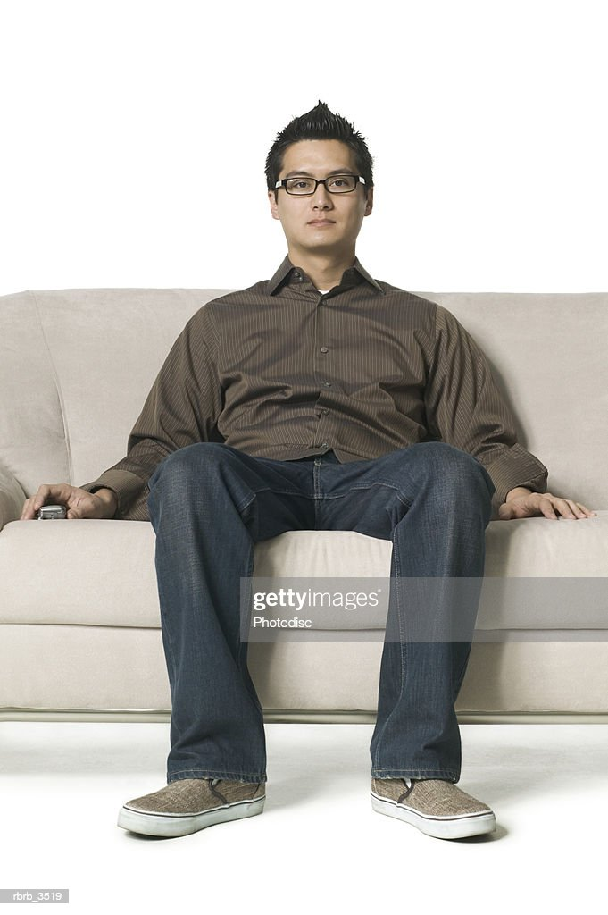 Portrait of a young man sitting on a sofa : Foto de stock