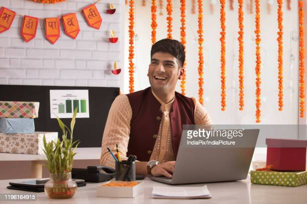 portrait of a young man sitting on his desk and working on his laptop on the occasion of diwali. - diwali decoration stock pictures, royalty-free photos & images