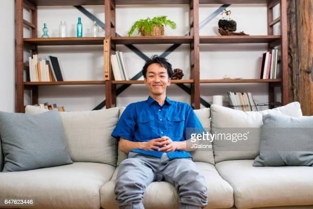 ソファーに座っている若い男の肖像 - 大人のみ ストックフォトと画像