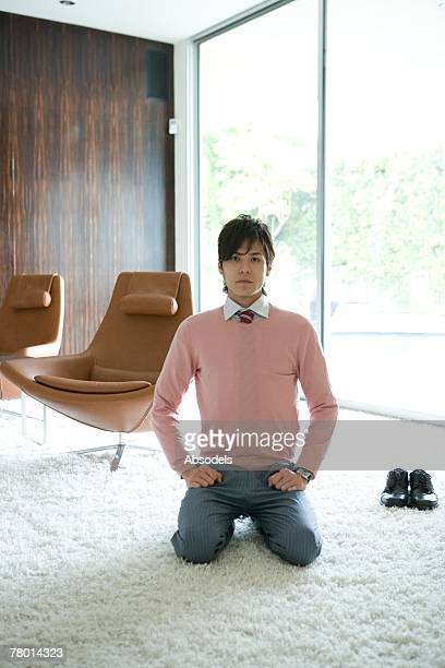 Portrait of a young man sitting straight in a room