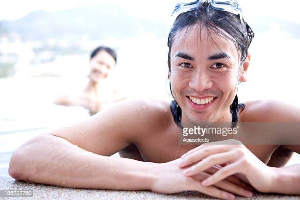 Portrait of a young man smiling at the poolside with a young woman in the background, Phuket, Thailand