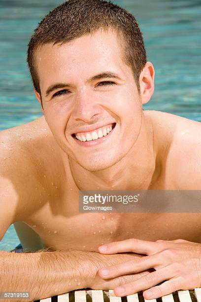 Portrait of a young man smiling in a swimming pool