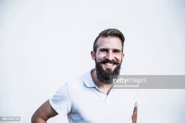 Portrait of a young man smiling in front of wall, Bavaria, Germany