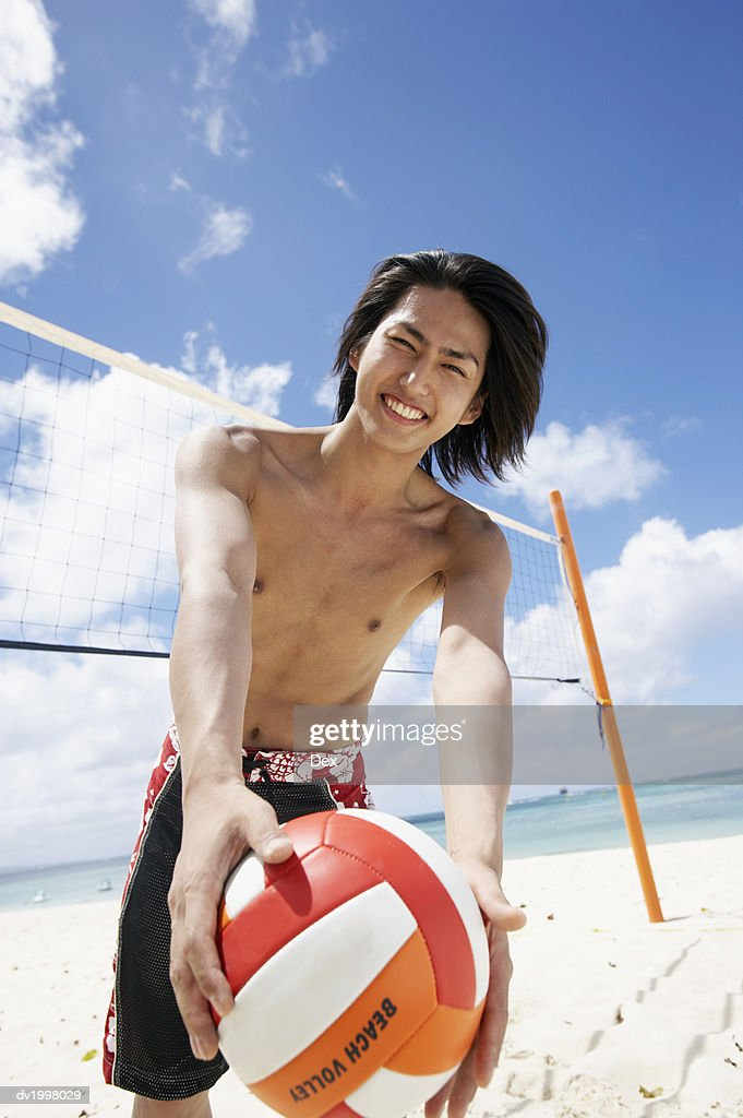 Portrait of a Young Man Standing by a Volleyball Net on the Beach and Holding a Ball : Stock Photo