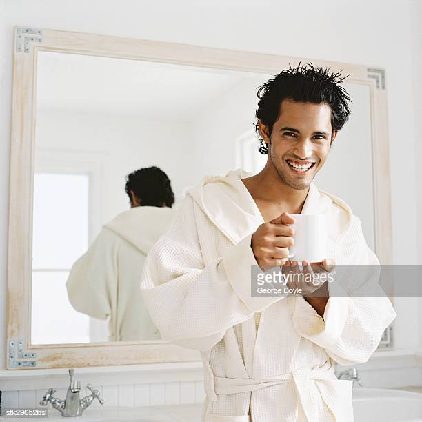 portrait of a young man standing in a bathrobe holding a mug