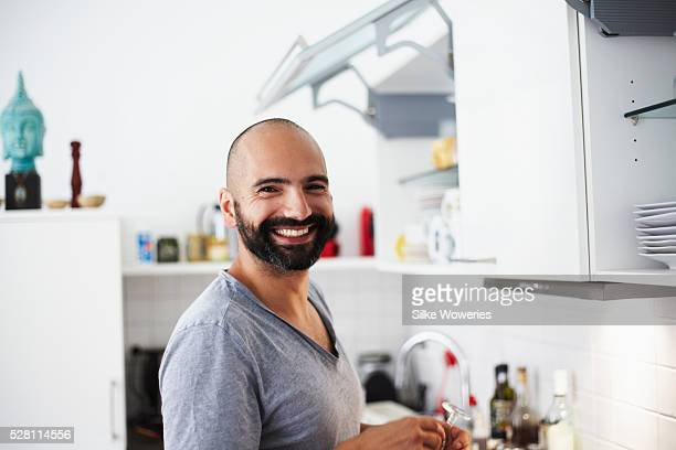 portrait of a young man standing in his kitchen and smiling