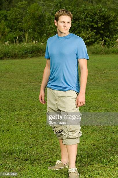 portrait of a young man standing in the garden - rolled up pants stock pictures, royalty-free photos & images