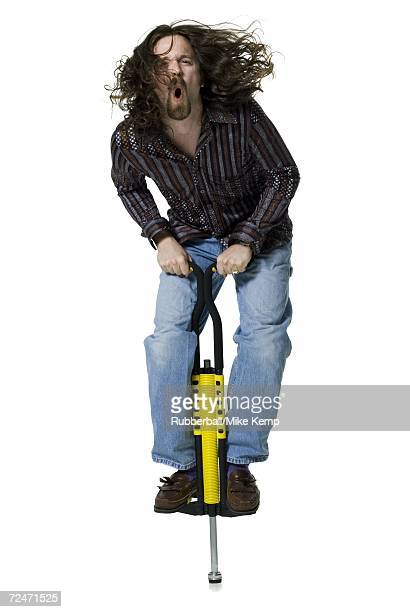 Portrait of a young man standing on a pogo stick