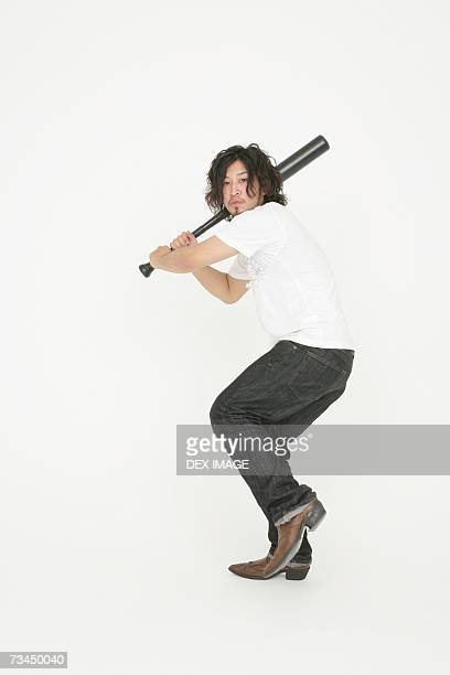 portrait of a young man swinging a baseball bat - sports bat stock pictures, royalty-free photos & images
