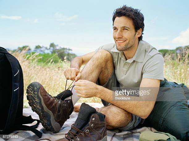 Portrait of a young man tying up his hiking boot