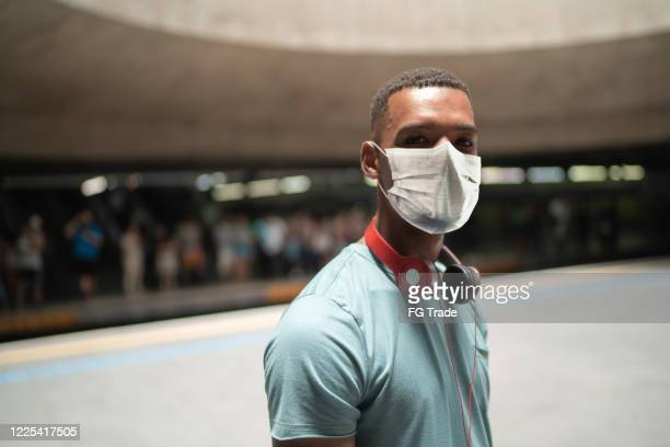 portrait of a young man using protective mask at metro station - pardo brazilian stock pictures, royalty-free photos & images
