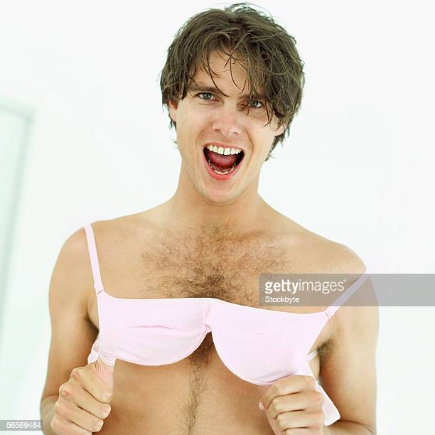 portrait of a young man wearing a bra - hairy chest stock-fotos und bilder