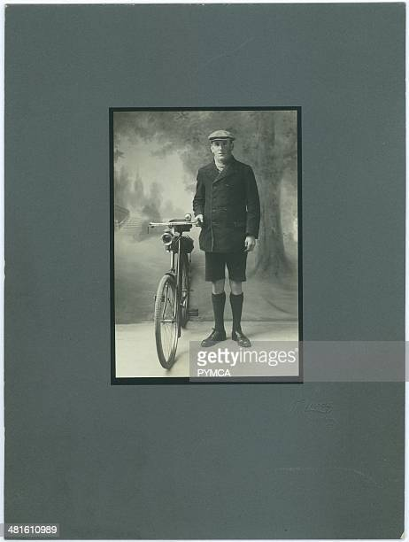 Portrait of a young man with a bicycle, circa 1910s.