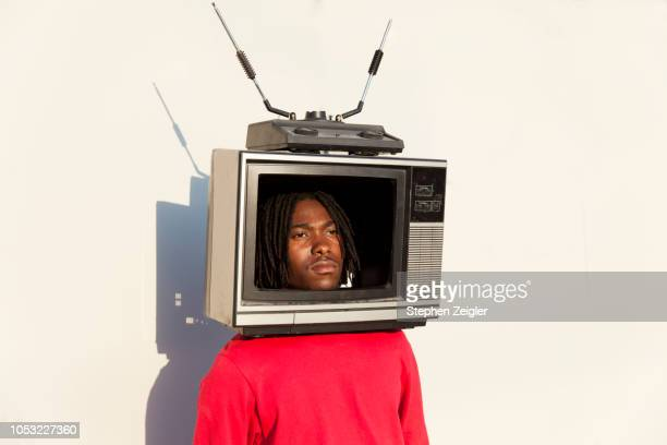 portrait of a young man with a tv set on his head - television industry stock pictures, royalty-free photos & images