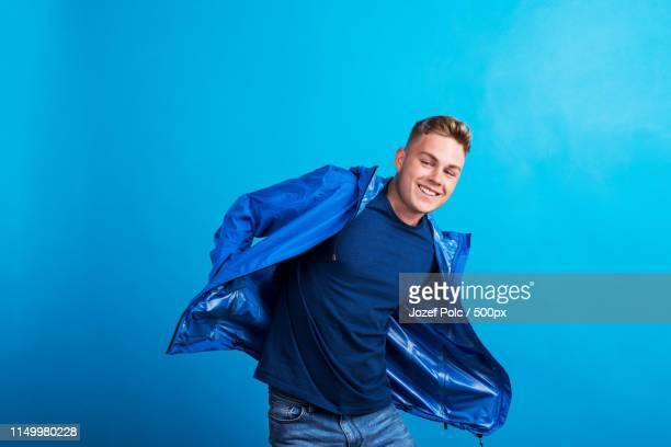 portrait of a young man with blue anorak in a studio, standing against blue background - portrait blue background stock pictures, royalty-free photos & images