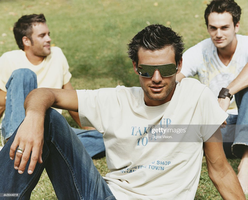Portrait of a Young Man With Friends on Grass Wearing Sunglasses : Stock Photo