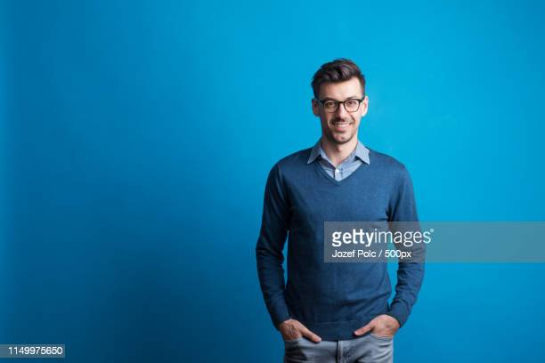 portrait of a young man with glasses in a studio on a blue background - portrait blue background stock pictures, royalty-free photos & images