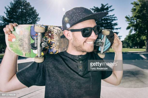 Portrait of a young man with skateboard at skatepark