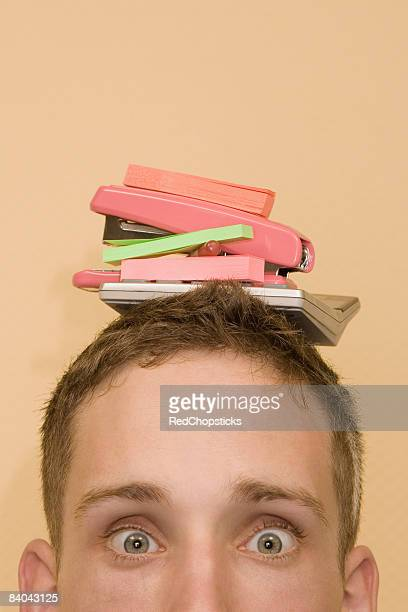 Portrait of a young man with stationery objects on his head