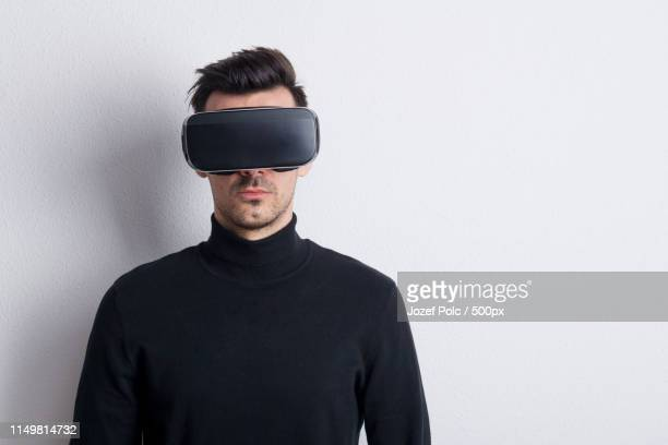 portrait of a young man with virtual reality goggles in a studio - タートルネック ストックフォトと画像