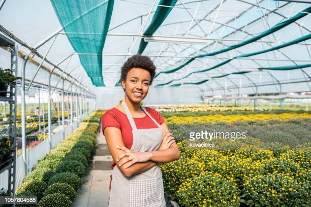 portrait of a young mixed race woman working in a greenhouse - botanist stock pictures, royalty-free photos & images