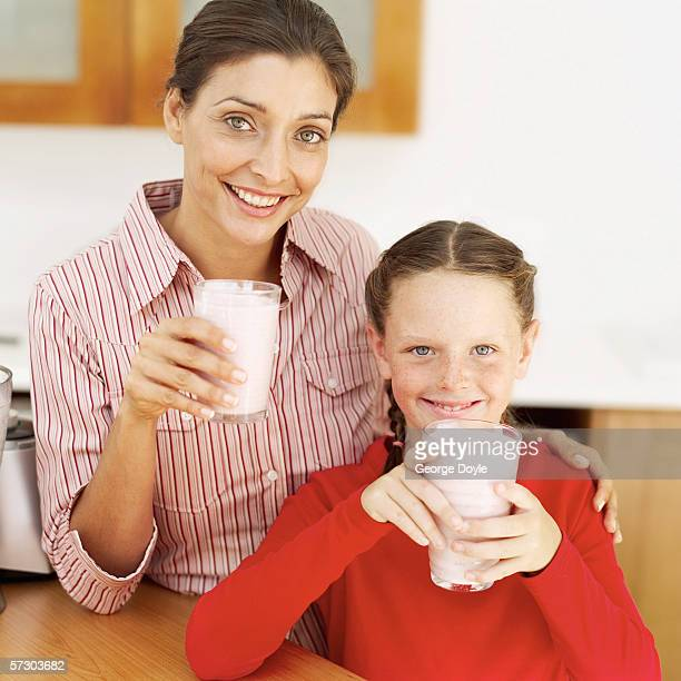 Portrait of a young mother and a young girl (8-10) holding glasses of strawberry milk shakes