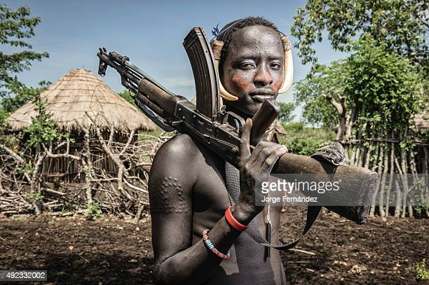 Portrait of a young mursi man holding a kalashnikov