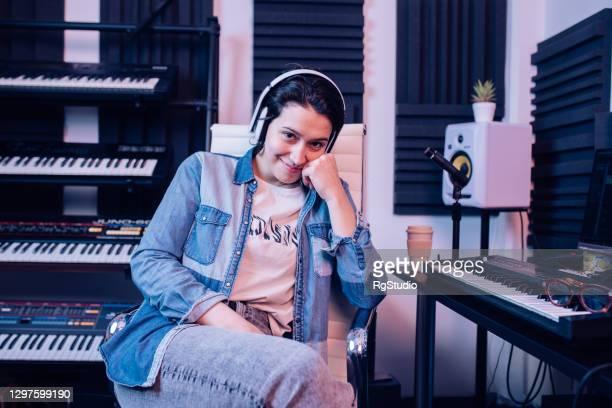 音楽スタジオの彼女の職場で若いミュージシャンの肖像画 - シンガーソングライター ストックフォトと画像