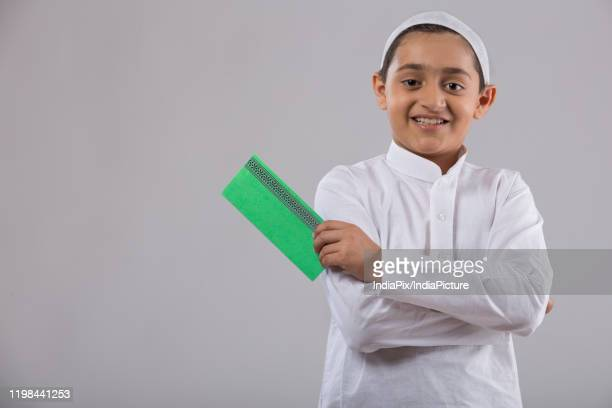 portrait of a young muslim boy holding an envelope - eid ul fitr stock pictures, royalty-free photos & images