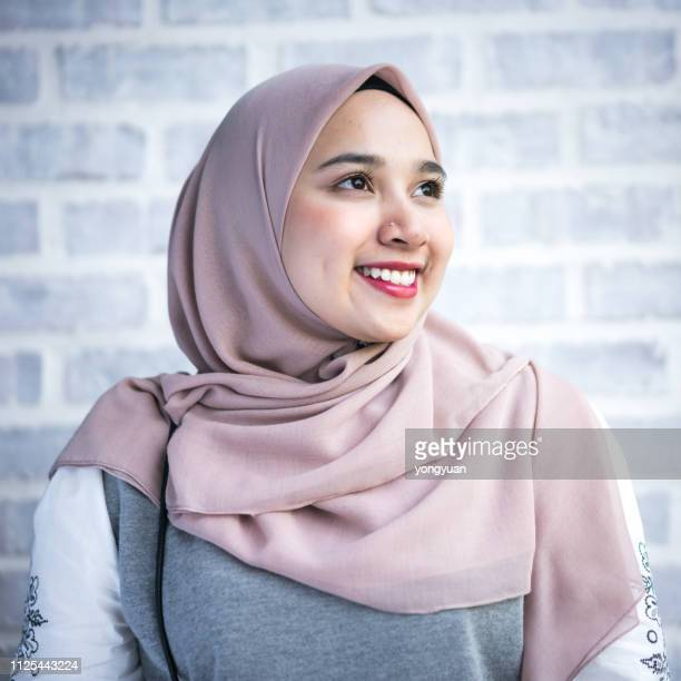 portrait of a young muslim woman wearing a hijab - chubby asian woman stock pictures, royalty-free photos & images